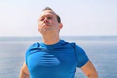 Corridore atletico di misura che fa allungando esercizio, preparante per l'allenamento di mattina su una spiaggia Immagini Stock