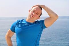 Corridore atletico di misura che fa allungando esercizio, preparante per l'allenamento di mattina su una spiaggia Fotografia Stock
