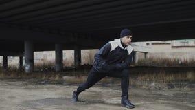 Corridore attraente dell'uomo che fa allungando esercizio per l'allenamento di mattina e pareggiando alla posizione urbana all'ap Immagini Stock
