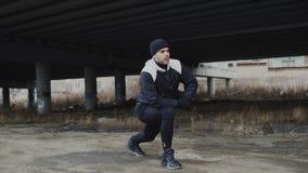 Corridore attraente dell'uomo che fa allungando esercizio per l'allenamento di mattina e pareggiando alla posizione urbana all'ap Fotografia Stock Libera da Diritti