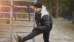 Corridore attraente dell'uomo che fa allungando esercizio che prepara per l'allenamento di mattina e che pareggia nel parco di in Immagine Stock Libera da Diritti