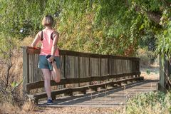 Corridore biondo della donna che fa allungamento del quadrato sul ponte di legno immagine stock libera da diritti