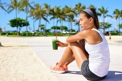 Corridore in buona salute della donna che beve frullato verde Immagini Stock Libere da Diritti