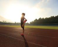 Corridore che allunga le gambe prima del funzionamento nel corso della mattinata soleggiata sulla pista dello stadio Immagine Stock Libera da Diritti