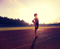 Corridore che allunga le gambe prima del funzionamento nel corso della mattinata soleggiata sulla pista dello stadio Fotografie Stock