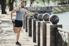 Corridore che fa allungando esercizio prima dell'allenamento Fotografia Stock
