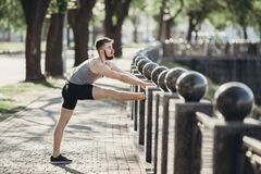 Corridore che fa allungando esercizio prima dell'allenamento Fotografie Stock