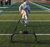 Corridore che tira una slitta con i pesi su un campo del tappeto erboso Fotografia Stock Libera da Diritti