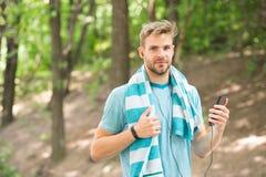Corridore con il mp3 il corridore dell'uomo ascolta musica sul riproduttore mp3 mp3 a disposizione del corridore dell'uomo sporti Fotografia Stock Libera da Diritti