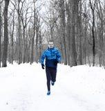 Corridore dell'uomo che corre nella foresta di inverno weared in giacca blu immagini stock libere da diritti