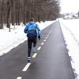 Corridore dell'uomo che corre sulla pista nell'orario invernale immagine stock libera da diritti
