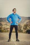 Corridore dell'uomo di sport che posa sul paesaggio asciutto del deserto nello stile di vita sano di forma fisica Immagine Stock