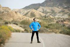 Corridore dell'uomo di sport che posa sul paesaggio asciutto del deserto nello stile di vita sano di forma fisica Immagine Stock Libera da Diritti
