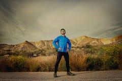 Corridore dell'uomo di sport che posa sul paesaggio asciutto del deserto nello stile di vita sano di forma fisica Immagini Stock
