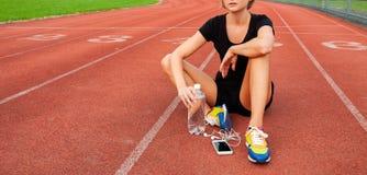 Corridore della donna in abiti sportivi che si siedono sull'eseguire stadio dopo il funzionamento fotografia stock libera da diritti