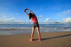 Corridore della donna che allunga armi prima dell'correre sulla spiaggia di alba Fotografia Stock Libera da Diritti