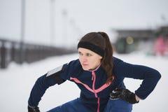 Corridore della donna che allunga le gambe prima che funzionato alla passeggiata di inverno della neve, fine su Fotografia Stock