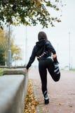 Corridore della donna che allunga le gambe prima del funzionamento Fotografia Stock