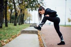Corridore della donna che allunga le gambe prima del funzionamento Immagine Stock Libera da Diritti