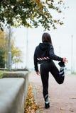 Corridore della donna che allunga le gambe prima del funzionamento Fotografia Stock Libera da Diritti
