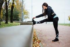 Corridore della donna che allunga le gambe prima del funzionamento Fotografie Stock