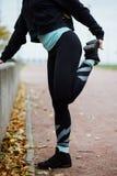 Corridore della donna che allunga le gambe prima del funzionamento Immagini Stock