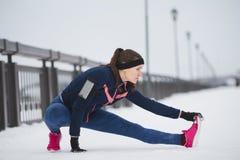 Corridore della donna che allunga le gambe prima del funzionamento Giovane risolvere della donna dell'atleta Concetto di forma fi Fotografia Stock