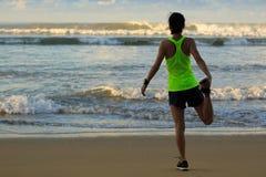 Corridore della donna che allunga le gambe prima dell'correre sulla spiaggia di alba Immagini Stock Libere da Diritti
