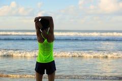 Corridore della donna che allunga le gambe prima dell'correre sulla spiaggia di alba Fotografia Stock