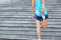 Corridore della donna che allunga le gambe sulle scale Immagine Stock