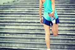Corridore della donna che allunga le gambe sulle scale Fotografia Stock Libera da Diritti