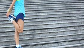 Corridore della donna che allunga le gambe sulle scale Fotografia Stock