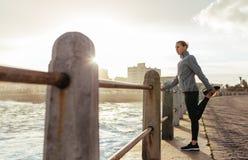 Corridore della donna che fa allungamento alla passeggiata della spiaggia Immagini Stock