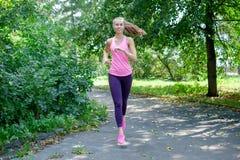 Corridore della donna che passa la strada del parco della molla Allenamento in un parco Bella ragazza di misura Modello di forma  Fotografie Stock