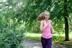 Corridore della donna che passa la strada del parco della molla Allenamento in un parco Bella ragazza di misura Modello di forma  Fotografie Stock Libere da Diritti
