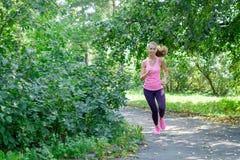 Corridore della donna che passa la strada del parco della molla Allenamento in un parco Bella ragazza di misura Modello di forma  Fotografia Stock Libera da Diritti