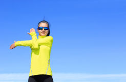 Corridore della donna di forma fisica che allunga armi prima dell'correre sul bea Fotografia Stock