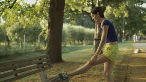 Corridore della donna di forma fisica che allunga le gambe prima del funzionamento archivi video