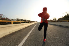Corridore della donna di forma fisica che allunga le gambe prima del funzionamento Fotografie Stock Libere da Diritti