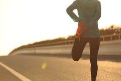 Corridore della donna di forma fisica che allunga le gambe prima del funzionamento Fotografia Stock Libera da Diritti