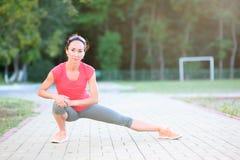 Corridore della donna di forma fisica che allunga le gambe prima del funzionamento Fotografia Stock