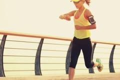 Corridore della donna di forma fisica che controlla il suo tempo di esercizio dall'orologio astuto alla spiaggia Immagini Stock