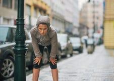 Corridore della donna nella pioggia che prende una rottura e un allungamento Fotografia Stock