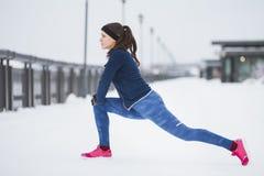 Corridore della giovane donna che fa esercizio di flessibilità per le gambe prima del funzionamento alla passeggiata di inverno d Immagine Stock Libera da Diritti