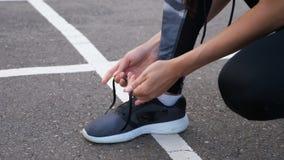 Corridore della ragazza che lega i pizzi per pareggiare le sue scarpe sulla strada in un parco archivi video