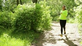 Corridore della ragazza di sport sul sentiero nel bosco in parco Giorno pieno di sole Fermi poi hanno resto archivi video