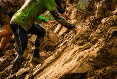 Corridore di corsa fangoso di ostacolo nell'azione Funzionamento del fango fotografie stock libere da diritti