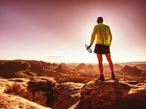 Corridore di misura nel vestito di sport che beve l'acqua dalla bottiglia di sport immagine stock