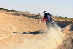 Corridore di motocross che slitta in una curva e che crea una nuvola di polvere fotografia stock