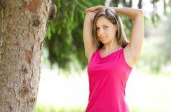 Corridore femminile attraente che allunga prima del suo allenamento Immagine Stock